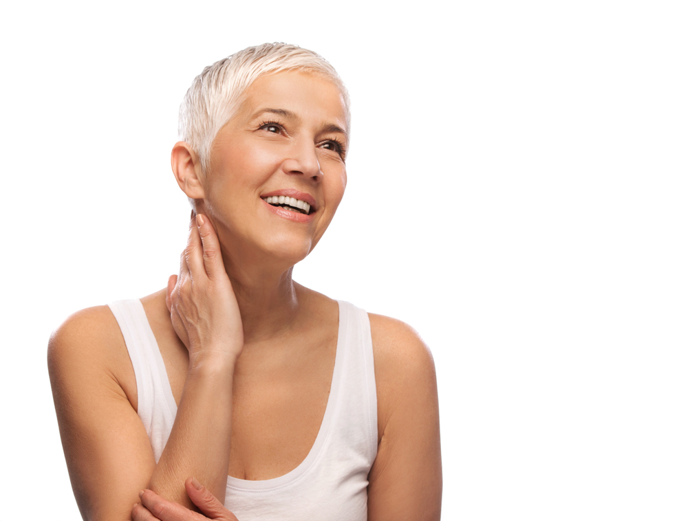 A woman with short, white hair smiles because of her excellent general dentistry care.